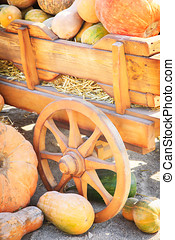 Many colorful pumpkins near a wooden cart on a sunny autumn...