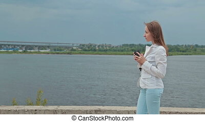 Beautiful girl standing on the embankment of the river with the phone