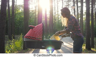 Mother with baby in stroller walking in park - Ufa, Russia....