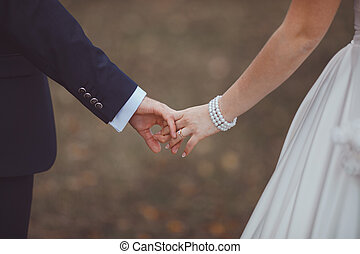 Hands of newlyweds - Groom and bride put trust in the future...