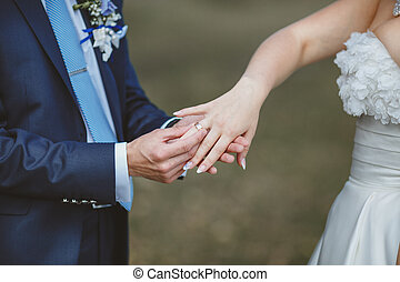 Hands of newlyweds - Groom puts wedding ring on brides...