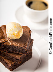 Brownie with ice cream and a cup of coffee on the table