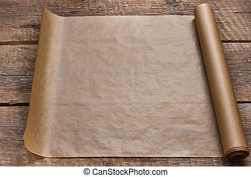 An open roll of paper on the wooden table background