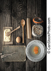 Recipe book, plate and ingredients for cookies on a wooden...