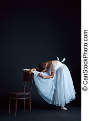 Portrait of the classical ballerina in white dress on black...