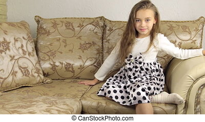 Beautiful little girl lies down on the sofa before going to...