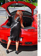 Lady packing car trunk - Young woman looking inside trunk...