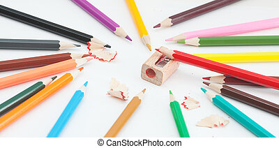 Colored pencils and sharpener on white. Photos school...