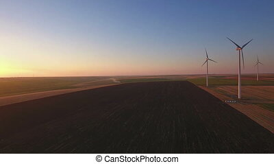Aerial view of cluster of wind turbines in agriculture...