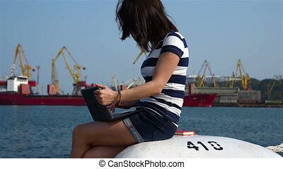 Girl Sitting With Laptop in Commercial Port Slow Motion...