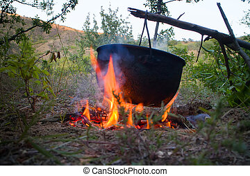 Camp life. On fire to boil pot of soup for traveler - Lunch...