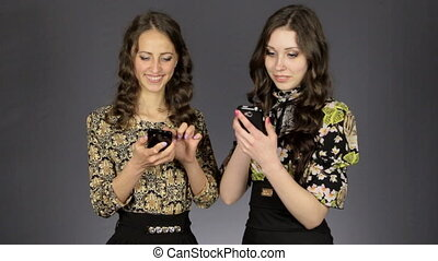 Two beautiful girls look at the phones screen, smile and...