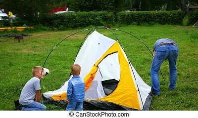 a man with kids gathering tent - a man with small kids...