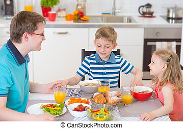 Nice family praying before eating breakfast together