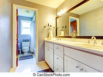 Simplistic bathroom with old style cabinets and tile trim.