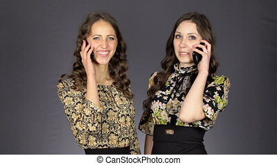 Two beautiful girls talking on the phone