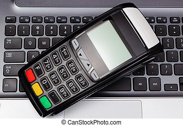 Payment terminal on laptop keyboard, finance and banking concept