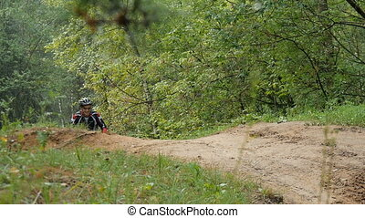 A cyclist rides on a small hill - Cyclist rides through the...