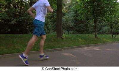 Male runner in white tshirt running in the park. 4K steadicam tracking video