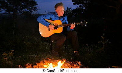Man playing an acoustic guitar in the woods