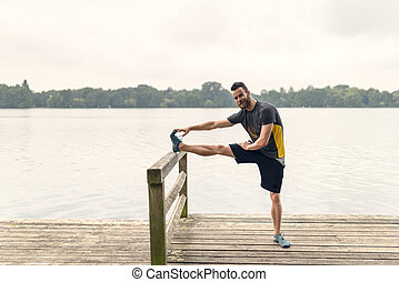 Young man doing stretching exercises on a deck - Young man...