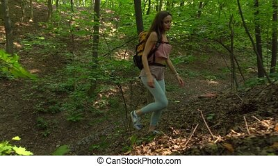 Beautiful young girl with backpack hiking uphill in sunny...