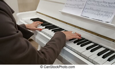 young lady plays on piano - young lady plays on white piano