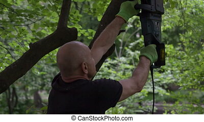 man works with electrical saw - man cuts trees branch wit...