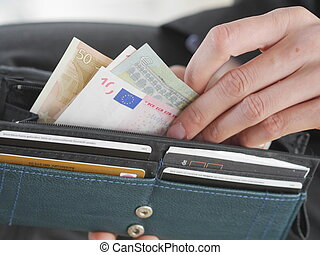 Euro money in wallet - close-up of female hand taking some...