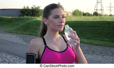 Fitness woman drinking fresh water from a plastic water outdoors in park. Slow motion