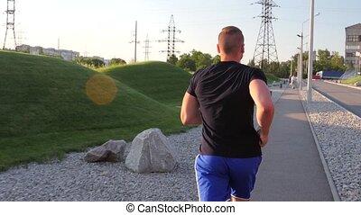 Men runner running on open road in countryside.