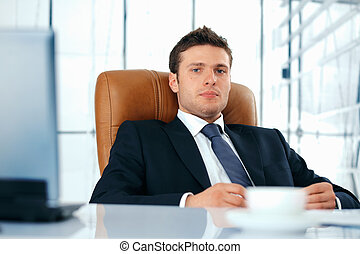 Young Boss. - Young business executive sitting relaxed in...