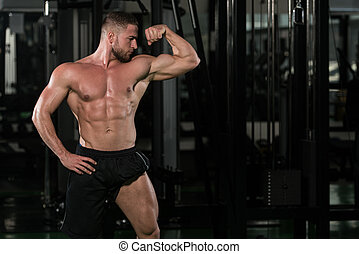 Muscular Man Flexing Muscles In Gym - Portrait Of A Young...