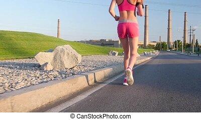 Sport footage, detail legs of woman running on empty street...