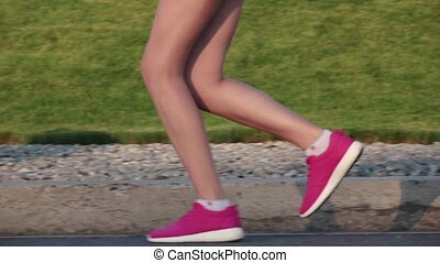 Female legs feet running on country road Slow motion -...