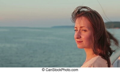 Portrait of young woman on cruise ship at sunset
