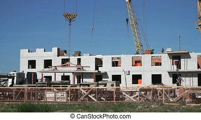 A construction crane delivers the concrete slab