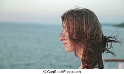 Close up shot of young woman on cruise ship at sunset. Two...