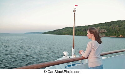 Young woman looking forward on cruise ship at sunset - Young...