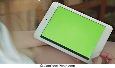 Woman looking at tablet computer with green screen in cafe