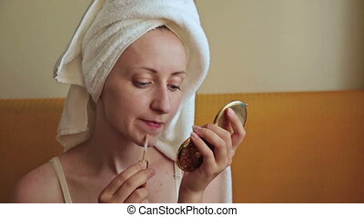 Young woman applies concealer foundation cream make up -...