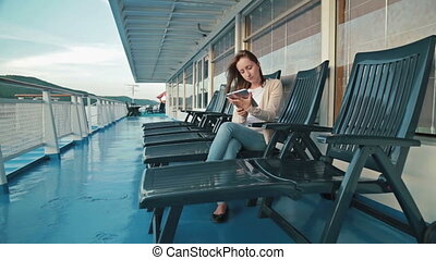 Woman using tablet on deck of cruise ship at sunrise - Woman...