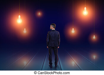 Back view of a businessman looking upwards at light bulbs glowing in the dark
