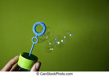 Bubble blower over green background