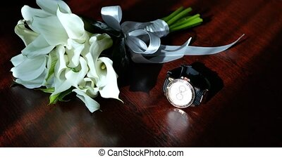 bouquet of flowers and trendy watch on the wood background