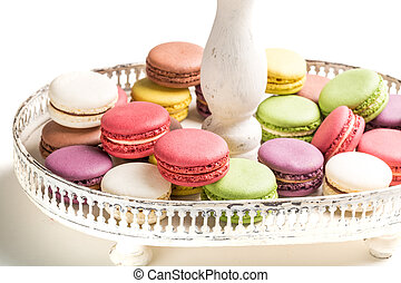 Delicious macaroons na plate on white background