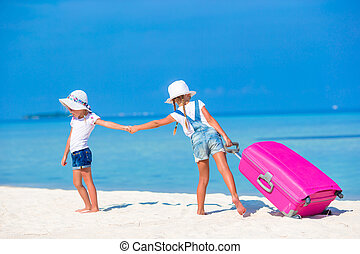 Little tourists girls with big suitcase on tropical white...
