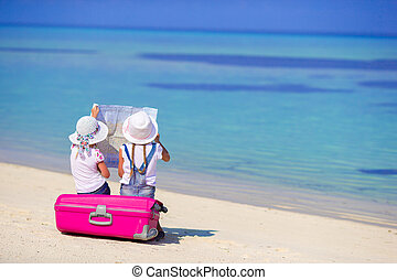 Little girls with big suitcase and map at tropical beach -...