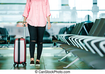 Closeup airplane passenger with passports and boarding pass and pink baggage in an airport lounge. Young woman in international airport walking with her luggage.