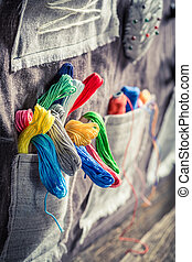 Handmade background made of threads, needles and buttons in...